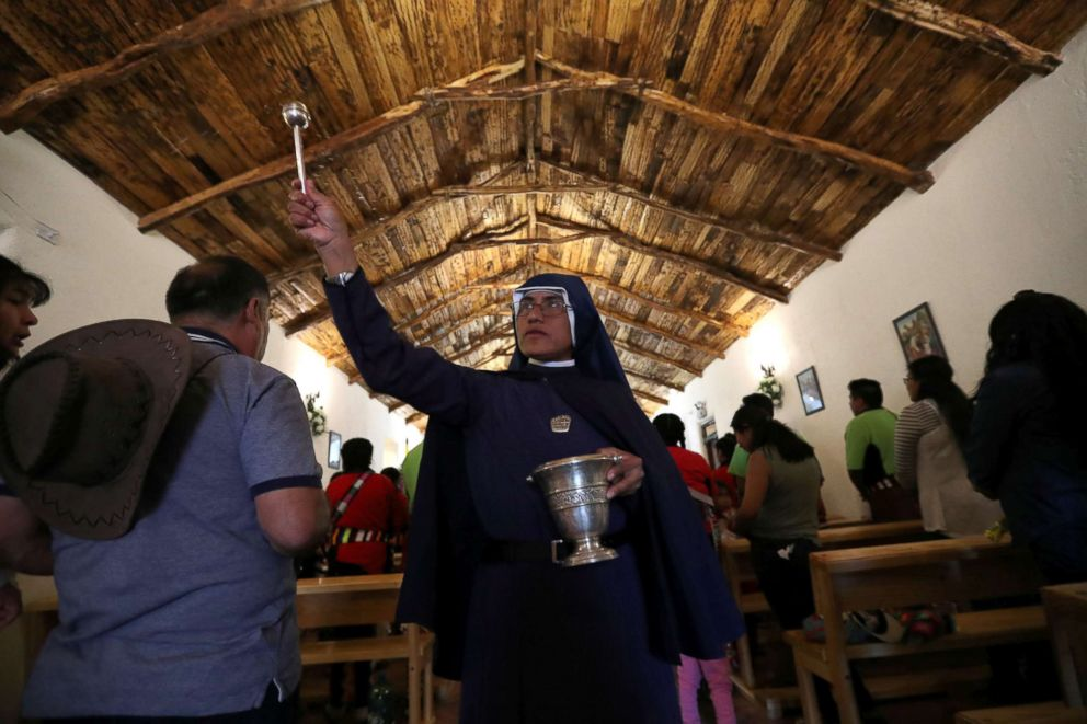 PHOTO: A nun sprinkles holy water on believers inside a church during a religious holiday in the Peine area on the Atacama salt flat in the Atacama desert, Chile, Aug. 15, 2018.