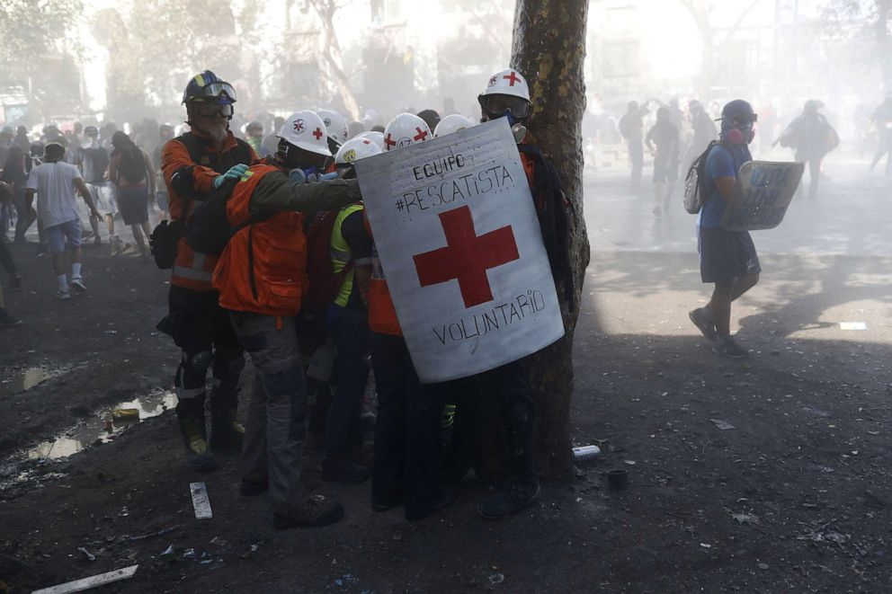 PHOTO: Medical personnel shield together to protect themselves from tear gas and rubber bullets during a protest against Chiles government in Santiago, Chile, Nov. 14, 2019.