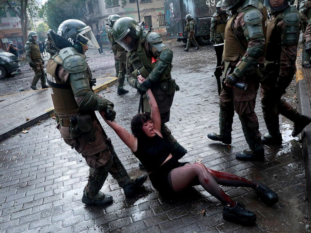 PHOTO: Riot police officers detain Camila Miranda after she was shot with 6 rubber bullets, 4 of which pierced her skin during a protest which she was demonstrating at against Chiles government in Santiago, Chile, Nov. 4, 2019.