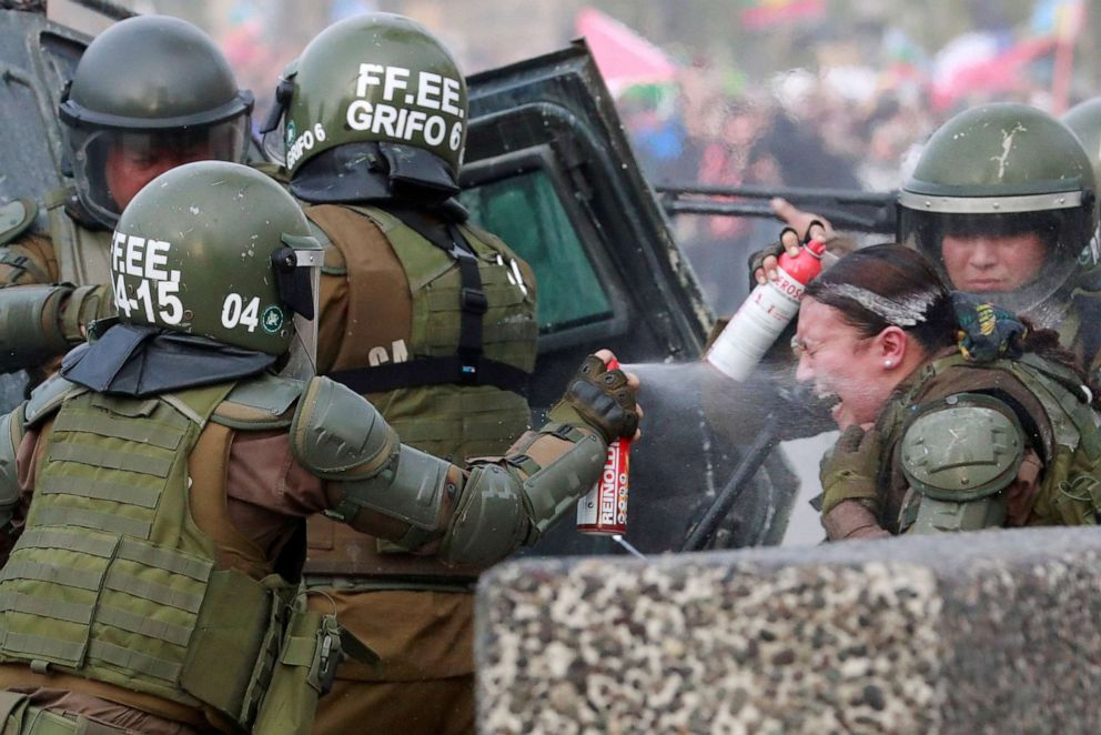 PHOTO: A riot police officer that was on fire is assisted by colleagues during a protest against Chiles government in Santiago, Chile, Nov. 4, 2019.