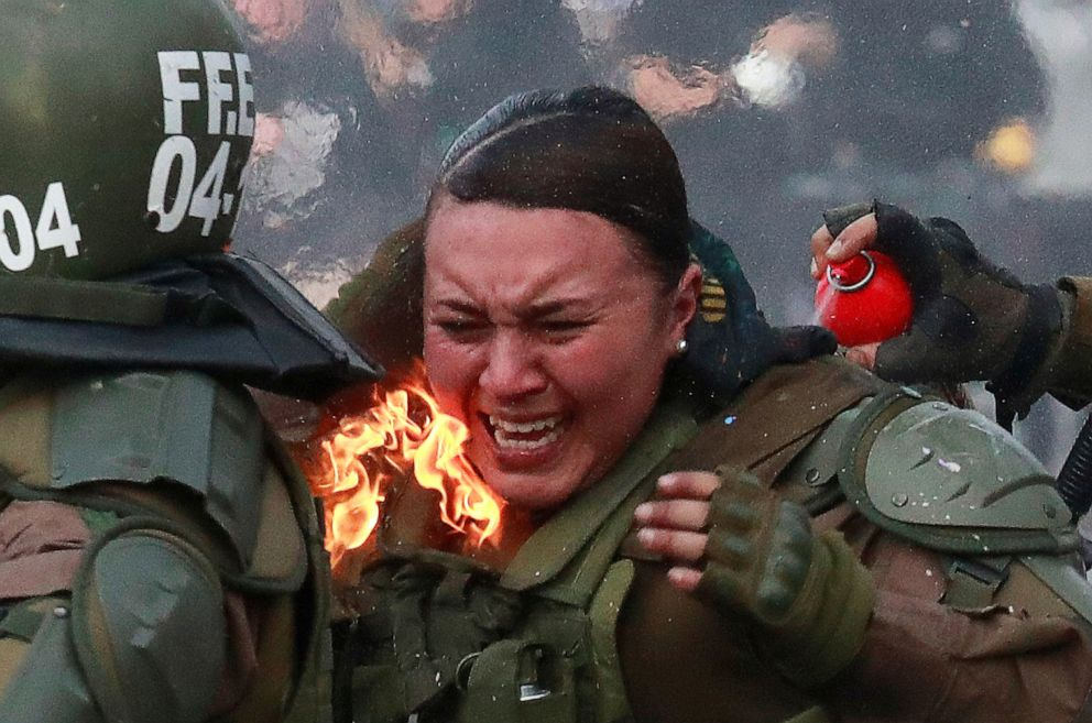 PHOTO: A riot police officer on fire is assisted by colleagues during a protest against Chiles government in Santiago, Chile, Nov. 4, 2019.