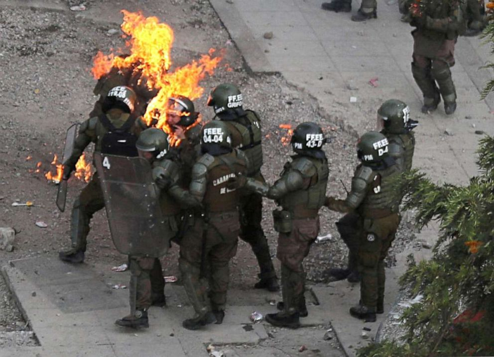 PHOTO: Riot police officers who are on fire are assisted by fellow officers during a protest against Chiles government in Santiago, Chile, Nov. 4, 2019.
