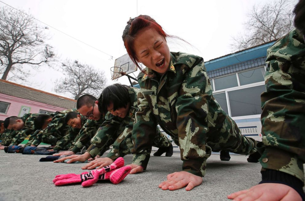 PHOTO: Students receive a group punishment during a military-style close-order drill class at the Qide Education Center in Beijing in this Feb. 19, 2014 file photo.