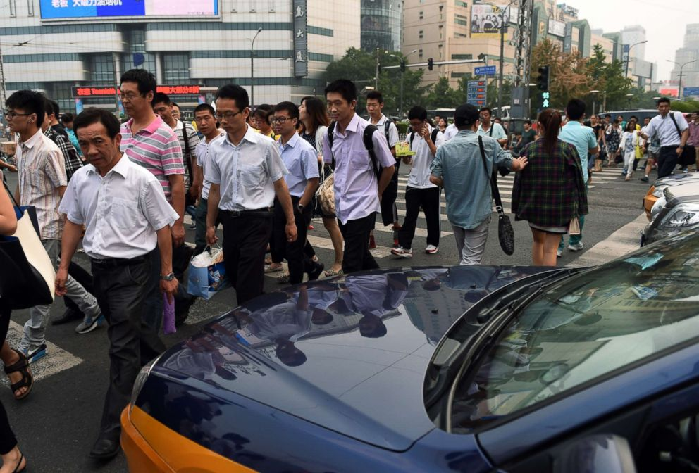 PHOTO: Pedestrians dodge around a taxi at a crossing in Beijing on June 10, 2014.