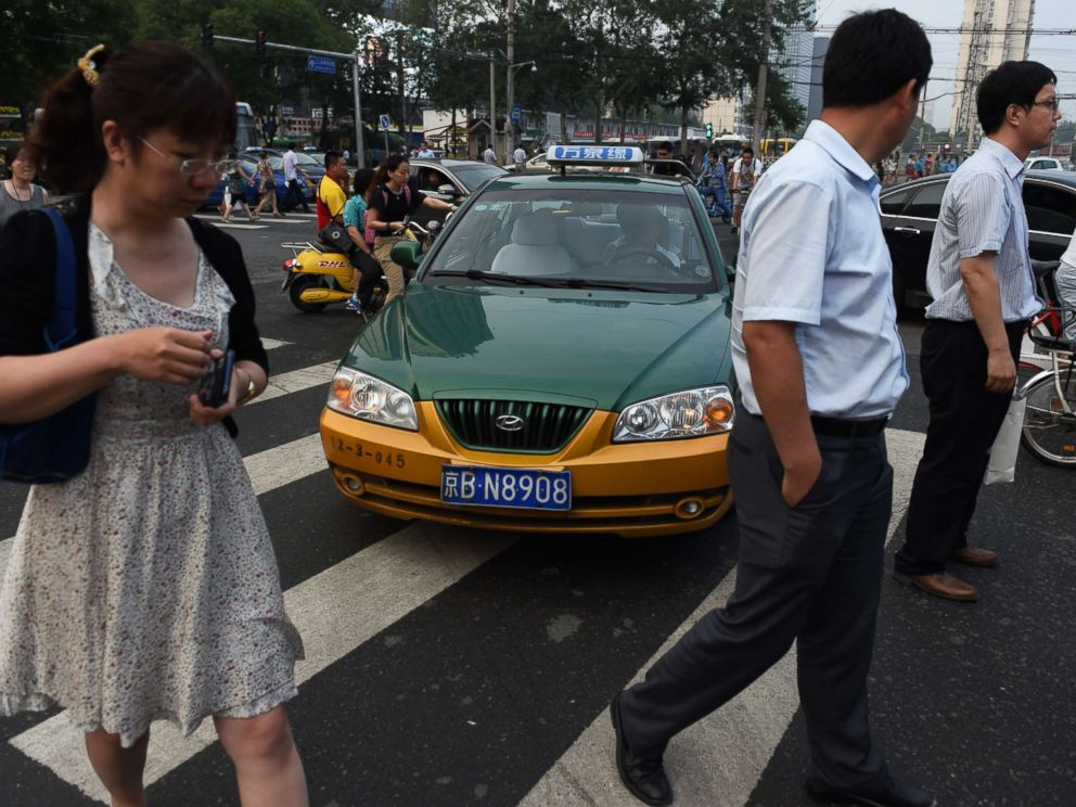 PHOTO: A taxi driver squeezes past people on a pedestrian crossing in Beijing on June 10, 2014.