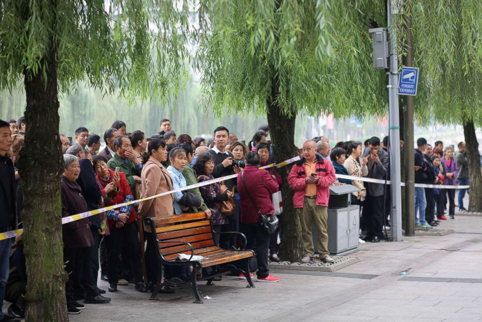 PHOTO: Local residents look on behind the police cordon after several kindergartners were stabbed by a woman on Oct. 26, 2018 in Chongqing, China.