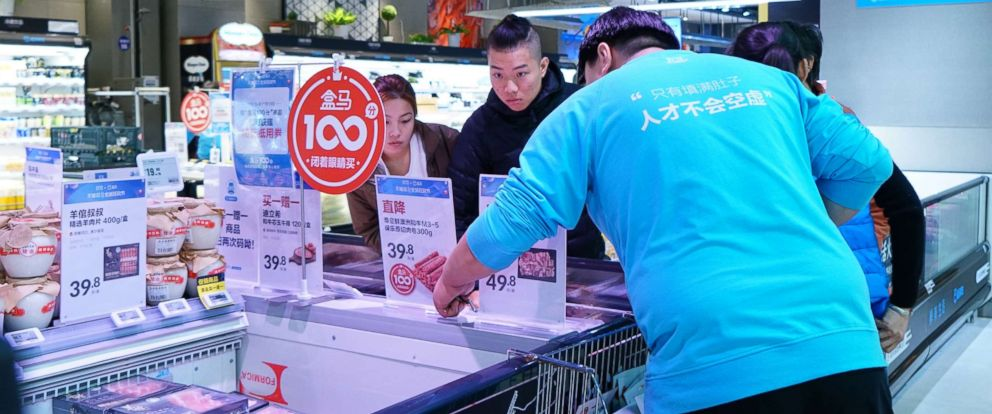 PHOTO: A young couple reads the discount information for imported goods while salesperson promotes the products, Nov. 7, 2018 in Beijing.