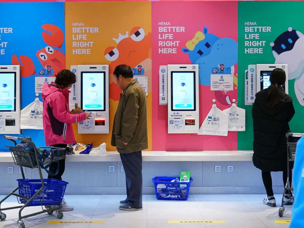 PHOTO: Shoppers use unmanned, cashless checkout machines to buy products with the Hema app on their phones in Beijing, Nov. 7, 2018.