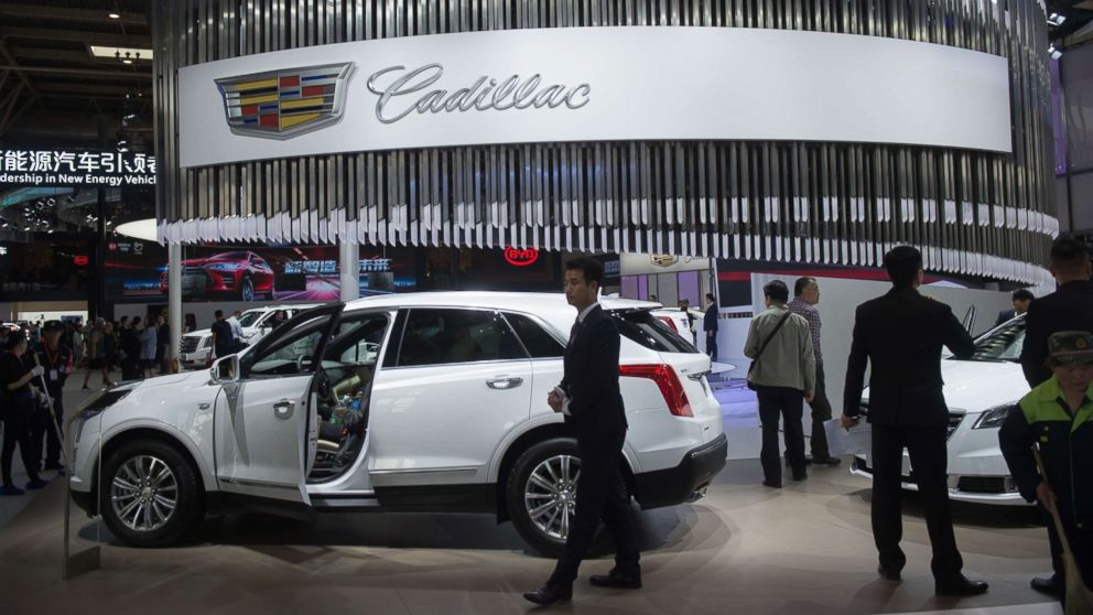 People walk through the Cadillac car display during the Beijing Auto Show in Beijing on April 25, 2018.
