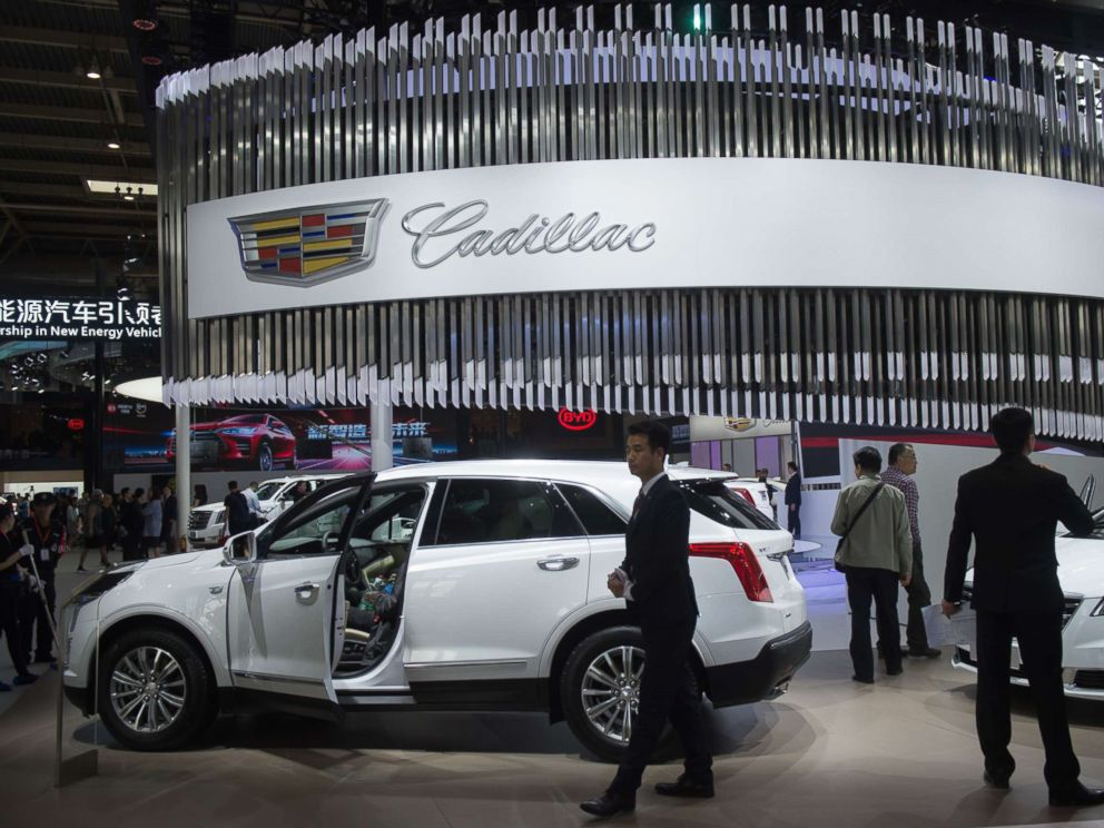 PHOTO: People walk through the Cadillac car display during the Beijing Auto Show in Beijing on April 25, 2018.
