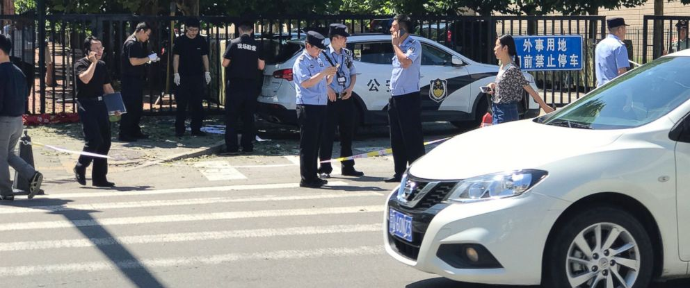 Officials and security personnel stand near the site of reported blast outside the U.S. Embassy in Beijing on Thursday.