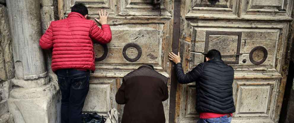 PHOTO: Visitors pray outside the closed doors of at the Church of the Holy Sepulchre, traditionally believed by many Christians to be the site of the crucifixion and burial of Jesus Christ, in Jerusalem, Feb. 25, 2018.