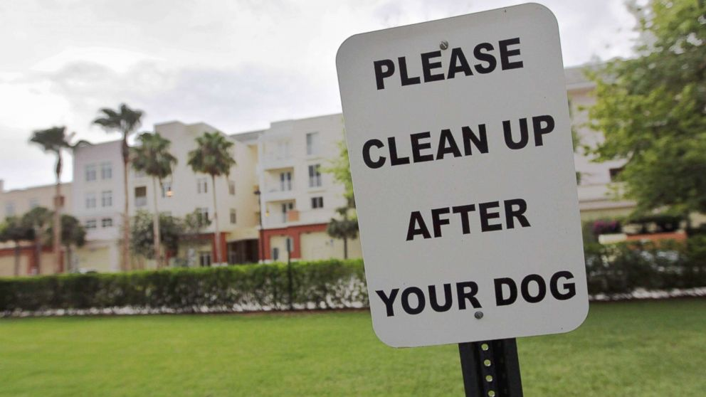 """A sign is posted reading, """" Please clean up after your dog""""' in The Village of Abacoa condominium complex in this June 30, 2011 file photo in Jupiter, Fla."""