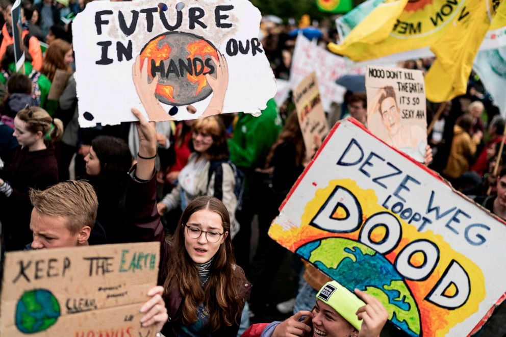 PHOTO: Protesters hold placards as they march during the Global Climate Strike organised by the Fridays For Future at the end of the global climate change week in The Hague, the Netherlands, on September 27, 2019.