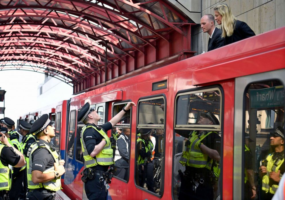 PHOTO: Police speak with protesters from the Extinction Rebellion campaign group who glued themselves to the top of a train at Canary Wharf station in London, April 17, 2019.