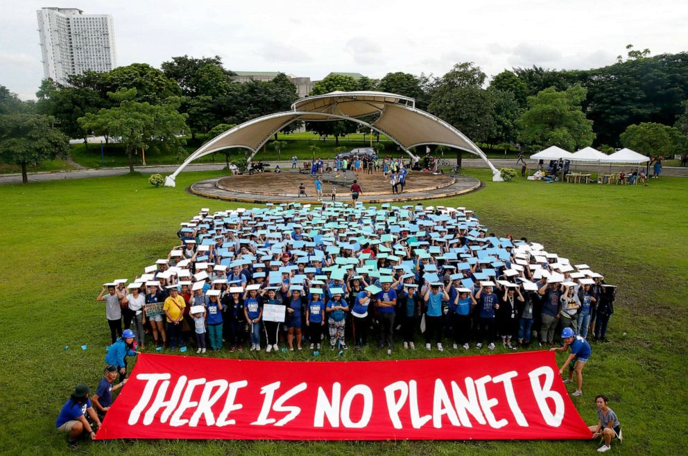 PHOTO: Environmental activists, mostly students, display their message in front of a human globe formation to coincide with the global protests on climate change Sept. 20, 2019, at the University of Philippines campus in Quezon city northeast of Manila.