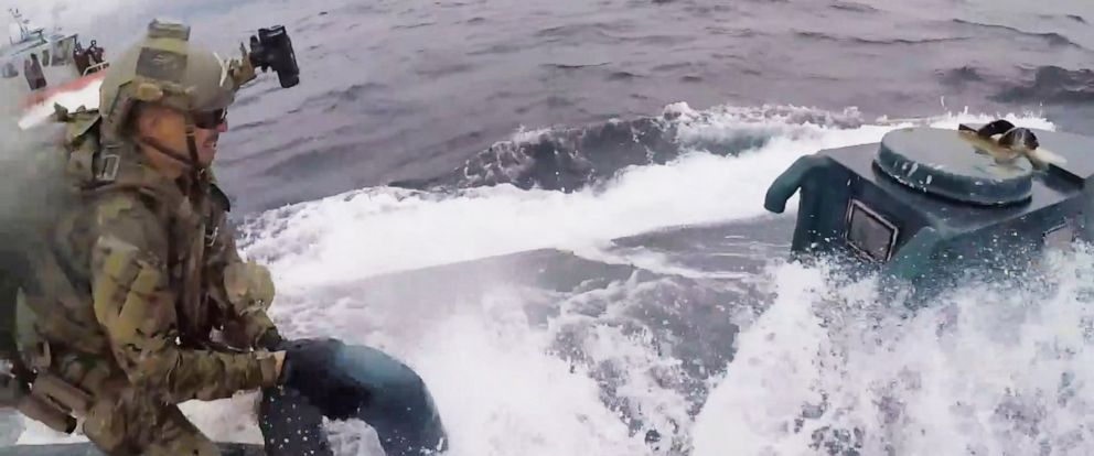PHOTO: An image made from video released by the U.S. Coast Guard shows a service member of the U.S. Coast Guard cutter Munro boarding a suspected drug smuggling vessel in international waters on the Pacific Ocean on June 18, 2019.