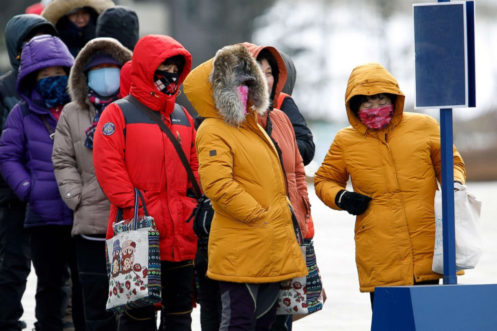People bundled up against the strong winds and the cold while they wait for a bus at the Pyeongchang 2018 Winter Olympic Games, Feb. 11, 2018.