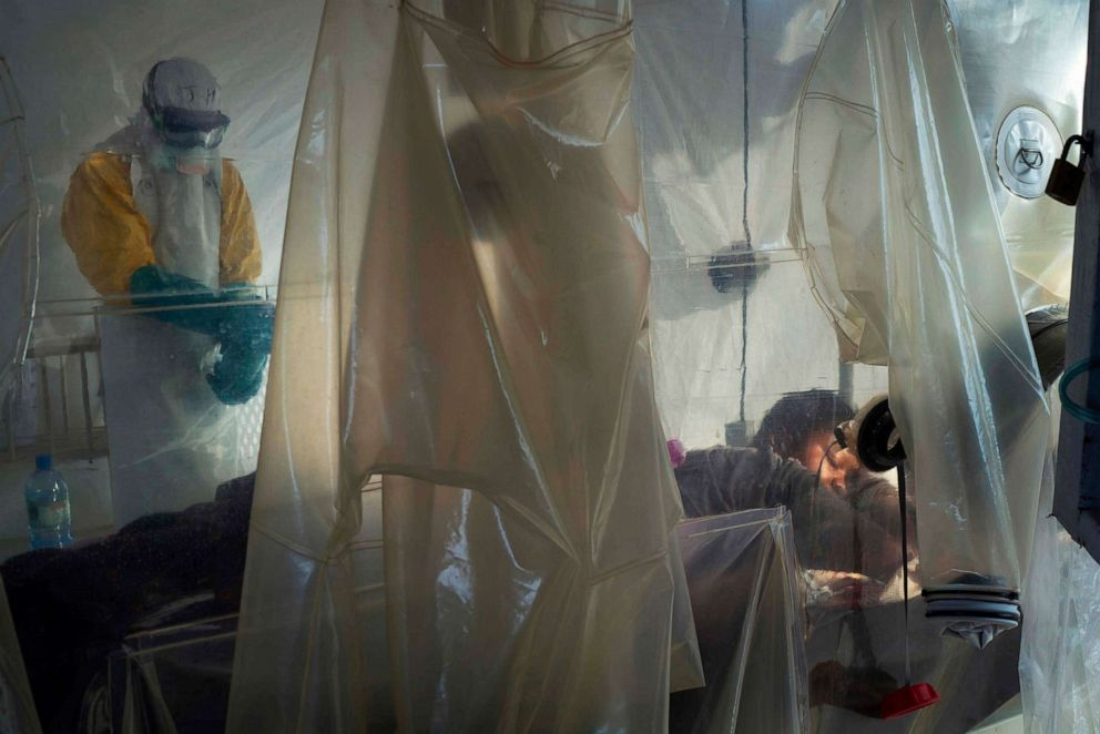 PHOTO: A health worker wearing protective gear checks on a patient isolated in a plastic cube at an Ebola treatment center in Beni, Congo, July 13, 2019.