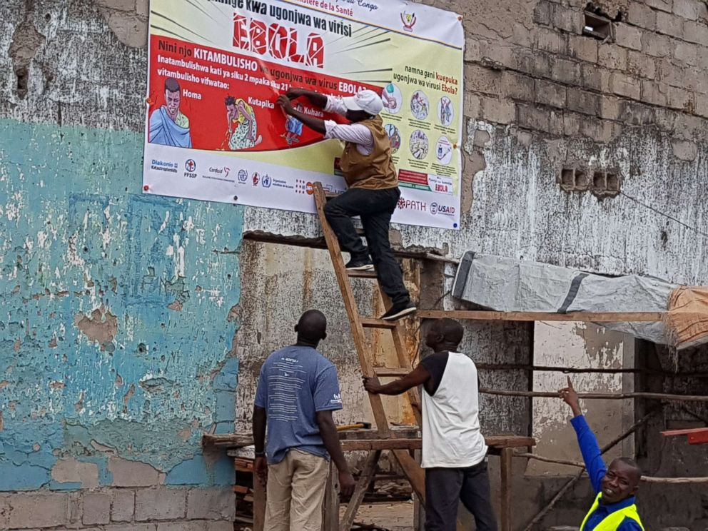 PHOTO: Workers fix an Ebola awareness poster in Tchomia, Democratic Republic of Congo, to raise awareness about Ebola in the local community, Oct. 9, 2018.