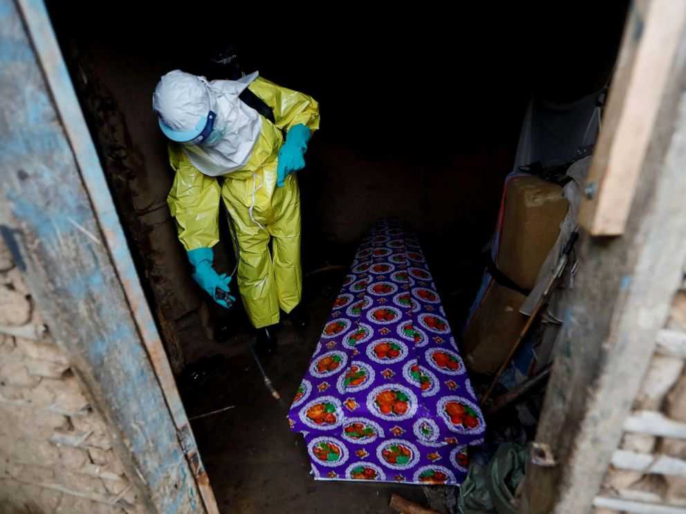 PHOTO: A healthcare worker, who volunteered in the Ebola response, sprays the coffin of a 85-year-old woman suspected of dying of Ebola, outside her house in Beni, in the Democratic Republic of Congo, Oct. 8, 2019.