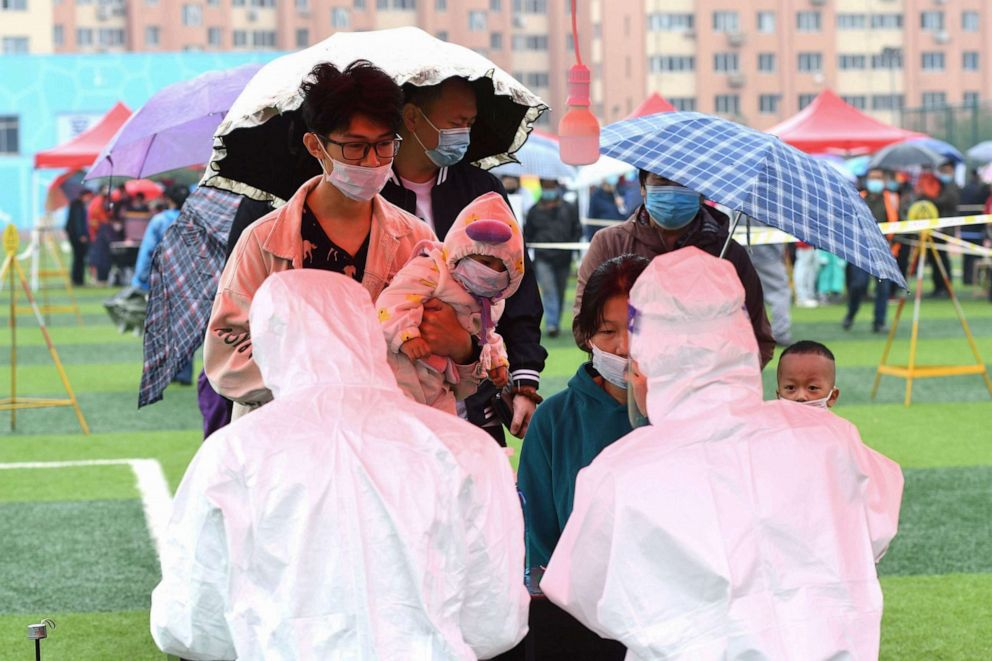 PHOTO: People line up in the rain to be tested for COVID-19 as part of a mass testing program following a new outbreak in Qingdao in China's eastern Shandong province on Oct. 14, 2020.