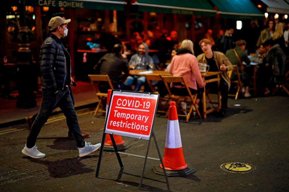 PHOTO: People drink at the outside tables of a cafe in London's Soho neighborhood on Sept. 24, 2020, on the first night of a new curfew for bars, pubs and restaurants in England and Wales, which was introduced to stem a surge of COVID-19 cases.