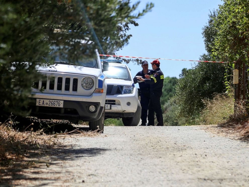 PHOTO: A police officer and a member of a fire brigade search and rescue team stand behind a police cordon, in an area where the body of a woman was found, near the village of Kolimpari on the island of Crete, Greece, July 9, 2019.