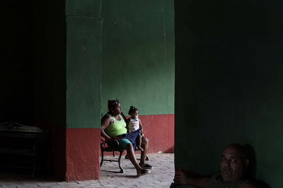 PHOTO: A woman and child sit in Trinidad, Sancti, Spiritus, Cuba on July 5, 2019. With a drop in tourism from about 20% to 30%, the small island nation is left with an uncertain future.
