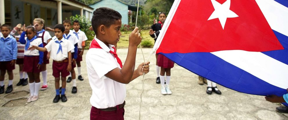 PHOTO: A boy raises the Cuban flag during a daily ceremony held at a school in the village of Santo Domingo, in the Sierra Maestra, Cuba, April 2, 2018.