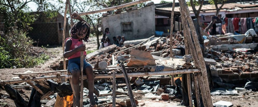 PHOTO: A girl sits on a kiosk destroyed by the cyclone Idai in Tica, Mozambique, March 24, 2019.