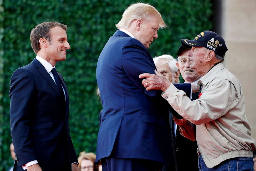 PHOTO: President Donald Trump and French President Emmanuel Macron, talk to a World War II veteran during a ceremony to commemorate the 75th anniversary of D-Day on June 6, 2019, in Colleville-sur-Mer, Normandy, France.