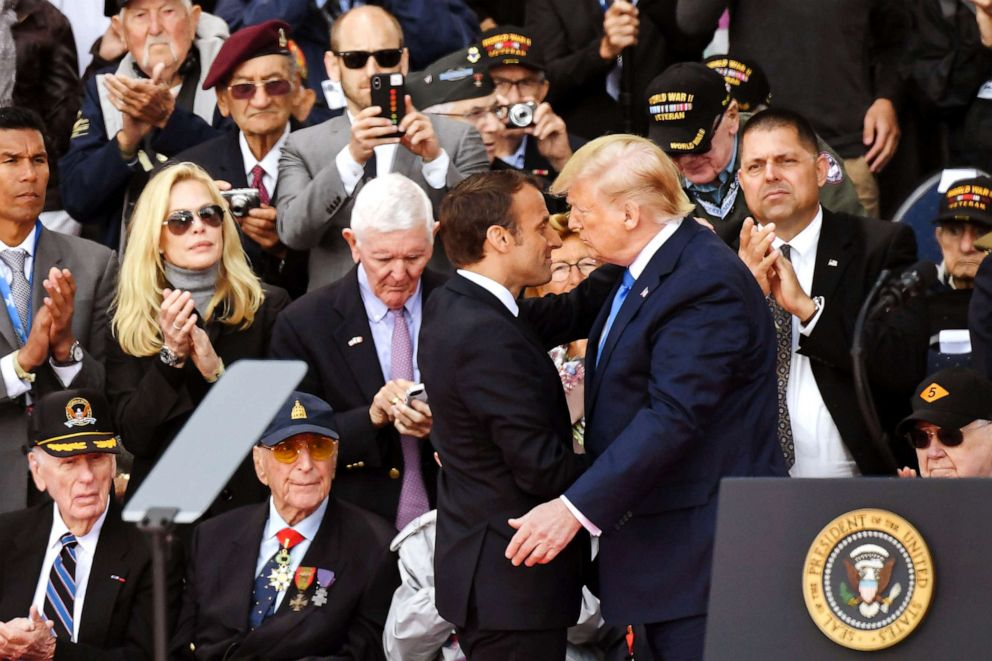 PHOTO: President Donald Trump and French President Emmanuel Macron hug in front of U.S. WWII veterans during a ceremony at the Normandy American Cemetery and Memorial in Colleville-sur-Mer, Normandy, northwestern France, on June 6, 2019.
