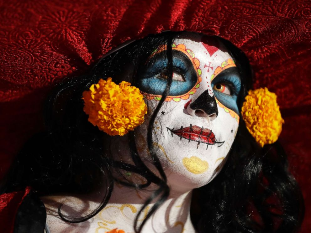 PHOTO: A woman dressed as Mexicos iconic Catrina awaits the start of the Grand Procession of the Catrinas, part of upcoming Day of the Dead celebrations in Mexico City, Oct. 22, 2017.