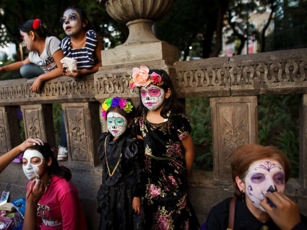 PHOTO: People have their faces painted in the style of Mexicos iconic Catrina, as they prepare to march in the Grand Procession of the Catrinas, part of upcoming Day of the Dead celebrations in Mexico City, Oct. 22, 2017.