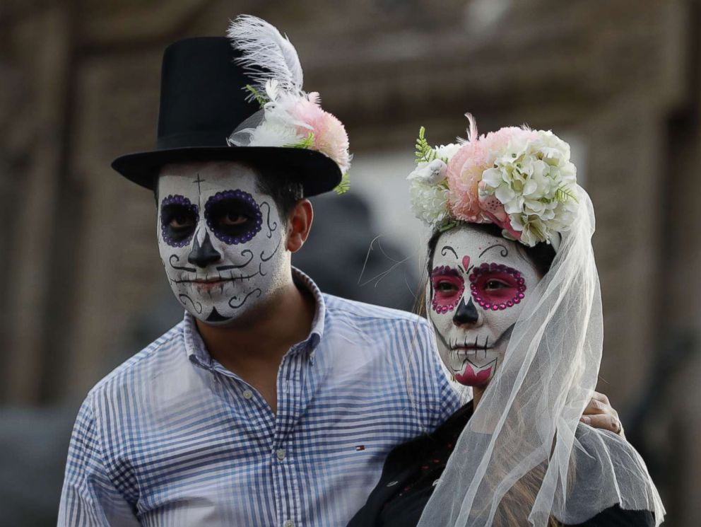 PHOTO: People dressed as a skeleton couple await the start of the Grand Procession of the Catrinas, part of upcoming Day of the Dead celebrations in Mexico City, Oct. 22, 2017.