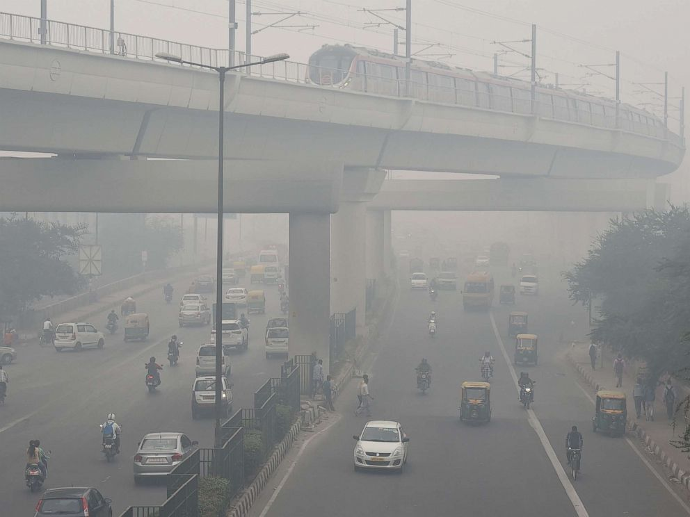PHOTO: A Delhi Metro train and vehicles drive past heavy smog in New Delhi, Nov. 5, 2018.