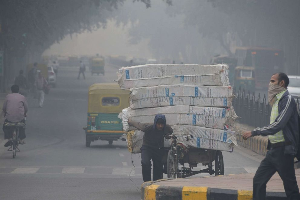 PHOTO: An Indian man with his face covered walks amid heavy smog along a street in New Delhi, Nov. 5, 2018.