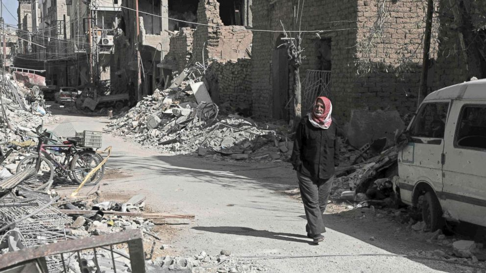 A Syrian man walks down a street past destroyed buildings, March 25, 2018, in Douma, in Eastern Ghouta on the outskirts of the capital Damascus.