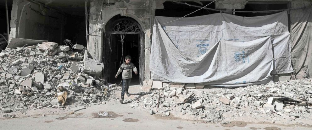 PHOTO: A Syrian child leaves a destroyed building, March 25, 2018, in Douma, in Eastern Ghouta on the outskirts of the capital Damascus.