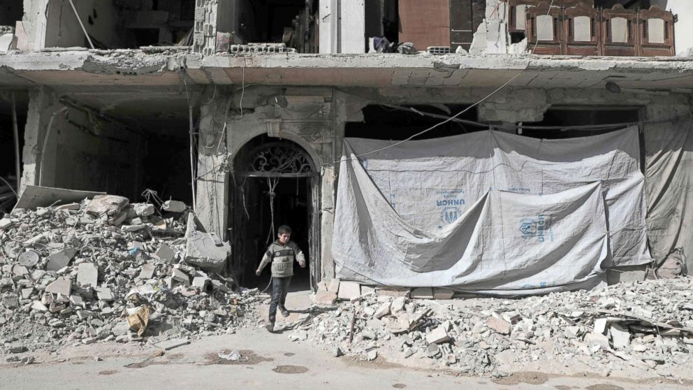 A Syrian child leaves a destroyed building, March 25, 2018, in Douma, in Eastern Ghouta on the outskirts of the capital Damascus.