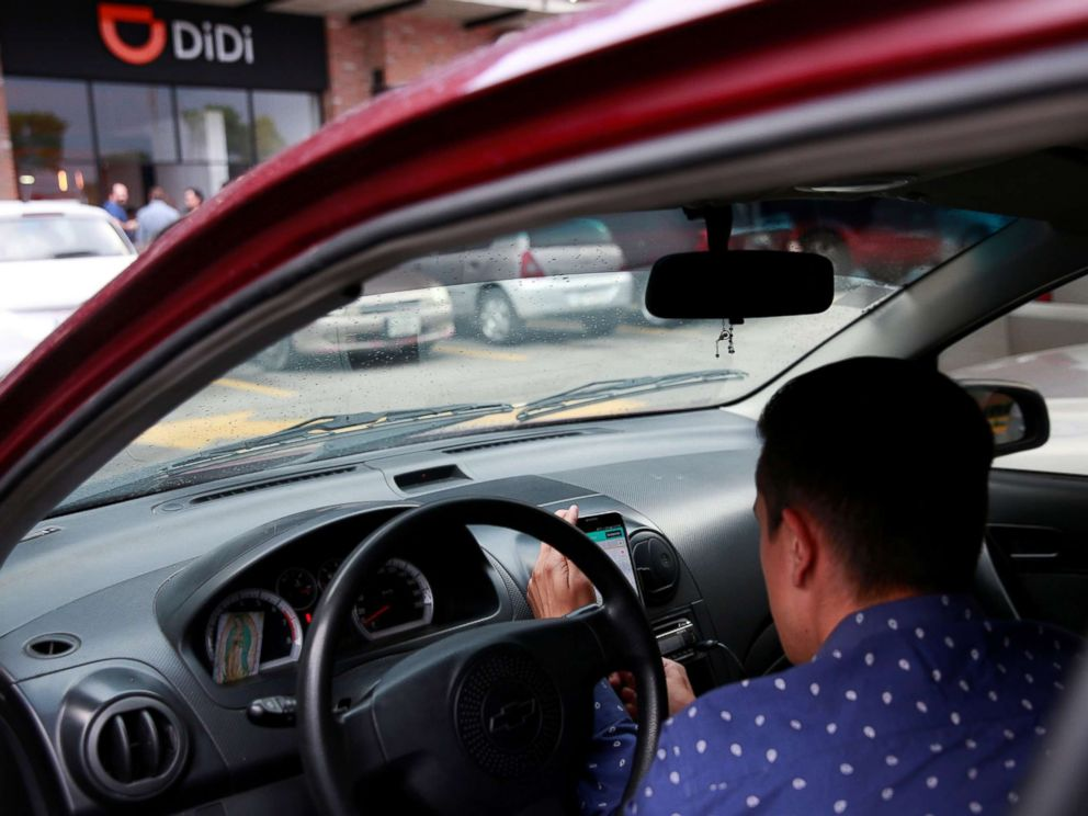 PHOTO: A new DIDI driver set up his mobile phone inside a car outside the new drivers center of the Chinese ride-hailing firm in Toluca, Mexico, April 23, 2018.