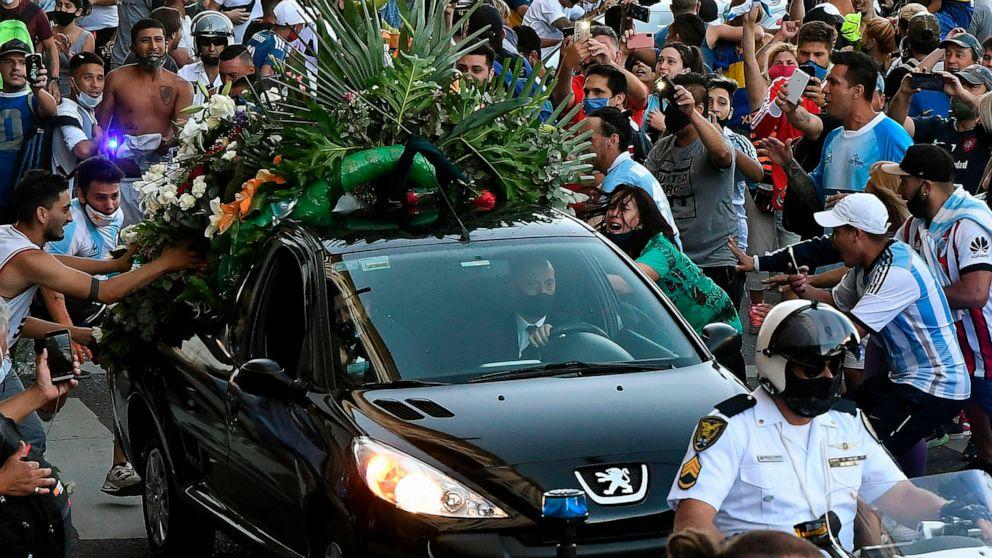 FOTO: Los fanáticos se agolpan junto al coche fúnebre que transporta a la leyenda del fútbol argentino Diego Maradona mientras salen del palacio presidencial de la Casa Rosada en Buenos Aires, Argentina, el 26 de noviembre de 2020.