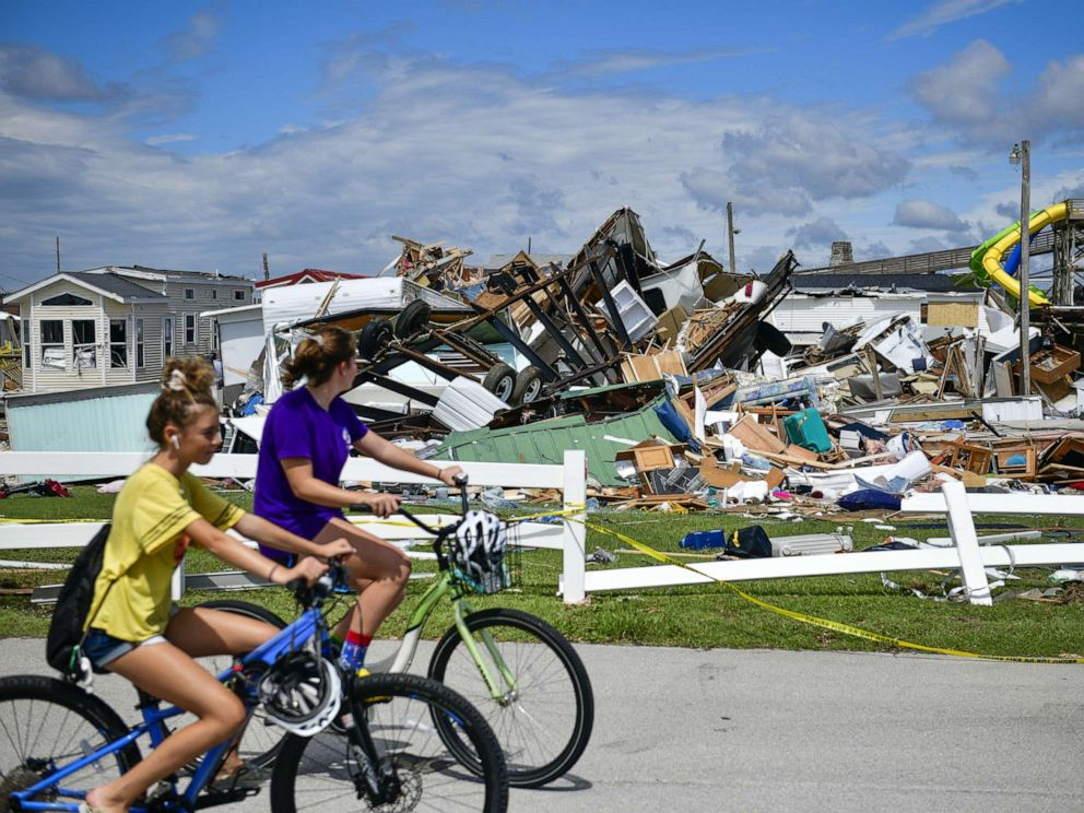 PHOTO: Residents ride bicycles past destroyed mobile homes in the Emerald Isle RV Park after a tornado touched down during Hurricane Dorian in Emerald Isle, N.C., Sept. 6, 2019.