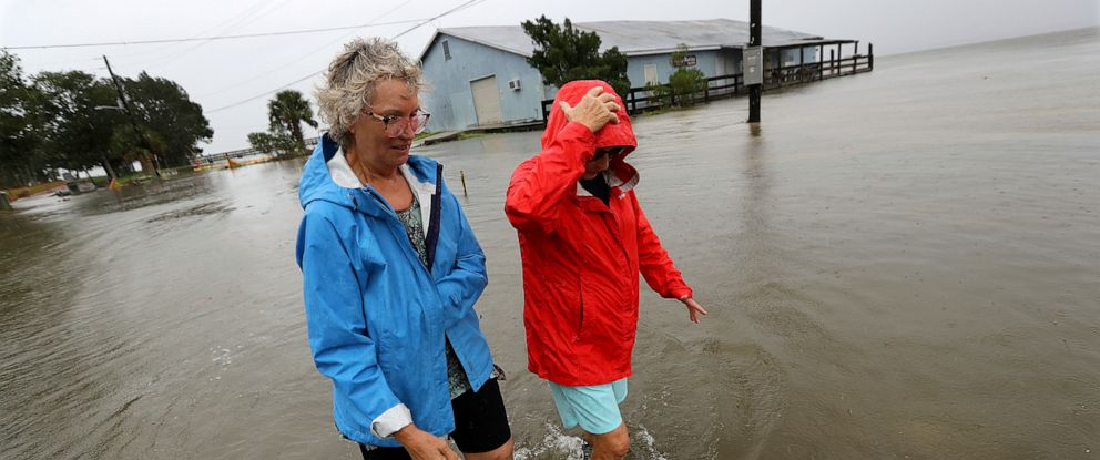 PHOTO: Jen Fabrick, left, and Anne Herring, right, walk through flood waters covering St. Marys Street at Langs Marina near their homes while Hurricane Dorian passes by, Sept. 4, 2019, in St. Marys, Ga.