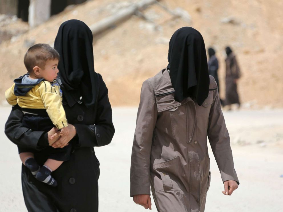 PHOTO: Civilians walk in the former Syrian town of Douma on the outskirts of Damascus, April 17, 2018,