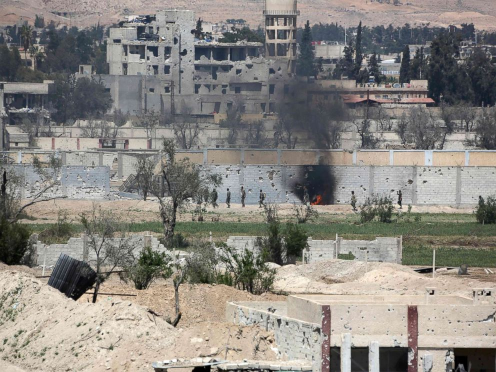 PHOTO: A picture taken on April 8, 2018, shows smoke billowing as Syrian Army soldiers advance in agricultural land on the eastern outskirts of Douma, as they continue their fierce offensive to retake the last opposition holdout in Eastern Ghouta.
