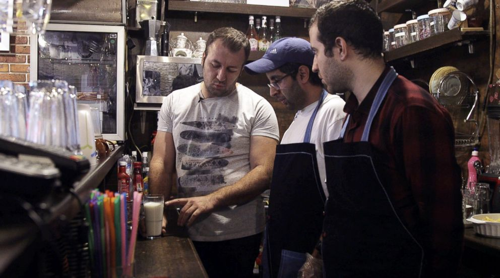 PHOTO: Staff members Shahriyar Sobhdel, center, and Mehdi Khakian, right, listen to a trainer at the Downtism Cafe, in Tehran, Iran, on Dec. 11, 2018.