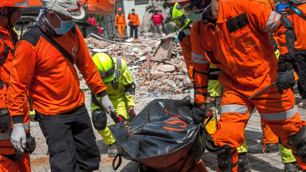 Rescuers recover the body of an earthquake victim from the ruins of the collapsed Roa Roa Hotel in Palu, Central Sulawesi, Indonesia, Tuesday, Oct. 2, 2018.