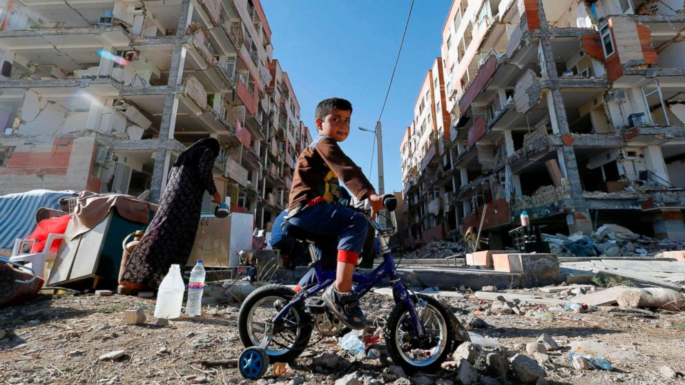 A boy rides a bicycle past earthquake damaged buildings in the town of Sarpol-e Zahab in Iran's western Kermanshah province near the border with Iraq, Nov. 14, 2017. A powerful earthquake struck the region on Nov. 12.